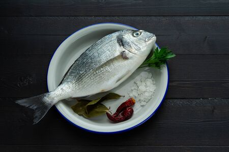 Bream in white plate on black background. Fish in black background. Top view. Copy space