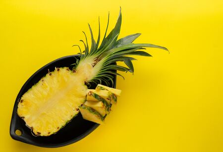 Pineapple cut in black ceramic bowl on yellow background. Reklamní fotografie