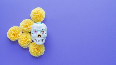 Mexican skull with yellow flowers of paper cempasuchil on violet background. Day of the Dead.