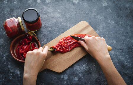 Frauenhände, die geröstete rote Paprika für die Verpackung vorbereiten. Vita überlegen.