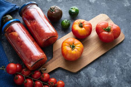 Tomatoes. Jars of canning and tomatoes of different kinds.