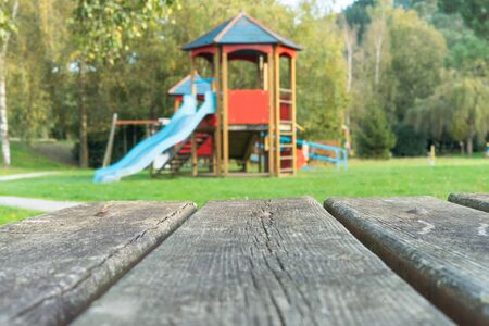 Rustic wooden table in a park with a children's playhouse in the background. Selective focus. Concept of nature. Foto de archivo