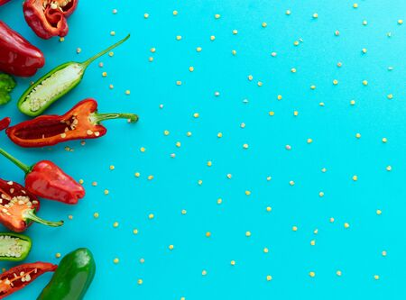 Peppers cut in half with seed pattern on blue background and space to the right. Copy space. Summer concept. Flat lay. Foto de archivo - 140648693
