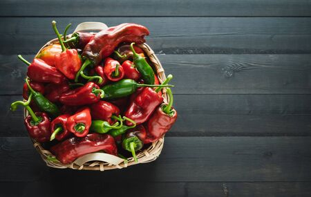 Wooden basket with red and green peppers on a black wooden base. Copy space on the right.
