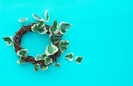 Rustic wooden crown with ivy on a blue background. Copy space. Congratulations concept.