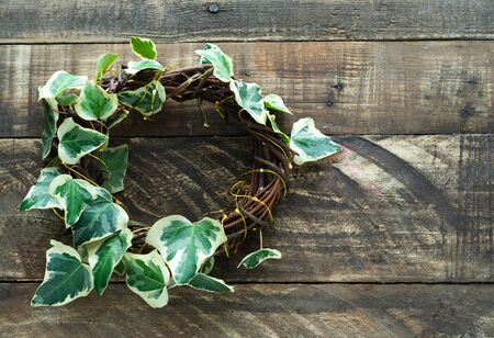 Rustic wooden crown with ivy on a dark wooden background. Copy space on the right. Congratulations concept.