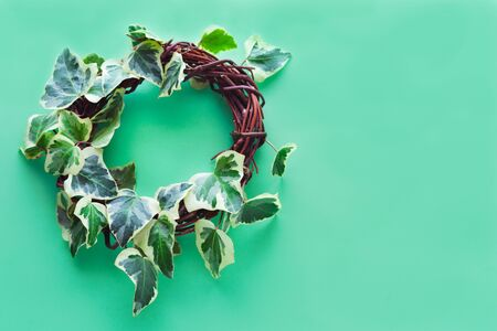 Ivy wreath on a blue background. Copy space. Congratulations concept. 版權商用圖片