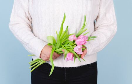 Woman in white sweater and black pants with pink tulip bouquet. Spring concept.
