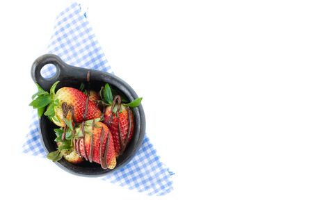 Black ceramic bowl with strawberries and chocolate on a white background. Healthy food concept.