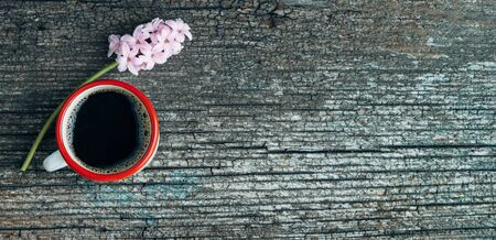 Coffee cup and pink hyacinth flower on old wood background. Copy space. Top view. 免版税图像