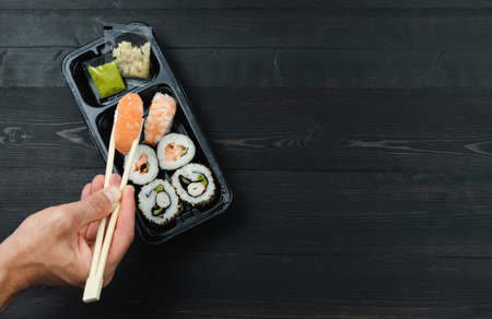 Hand with chopsticks and sushi tray. Take-away concept. Copy space.
