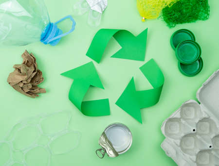 Recycling logo on green background with objects to recycle.