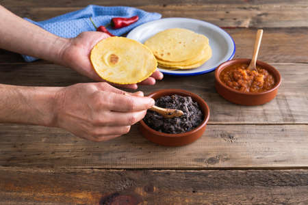 Process of making Mexican breakfast eggs for ranchers on a wooden base. Mexican cuisine. Copy space.