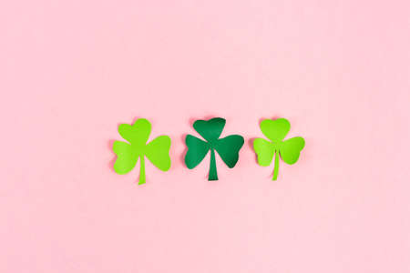 St. Patrick's Day celebration, three shamrocks on pink background. Copy space.