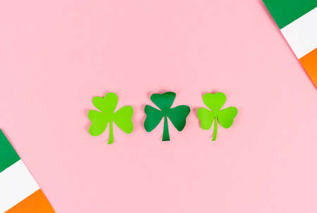 St. Patrick's Day. Three clover leaves with Irish flags on cream background. Copy space. Top view.