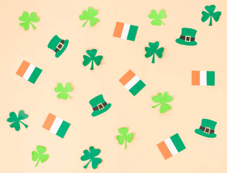 St. Patrick's Day pattern with paper cutout figures on pink background. Flat lay. Top view.