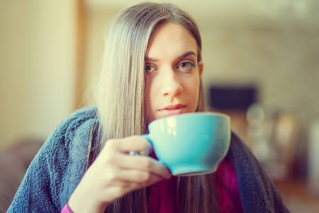 Beautiful blonde woman holding cup of tea or coffee. Looking at window and drink tea. Good morning with tea. Archivio Fotografico - 131463162