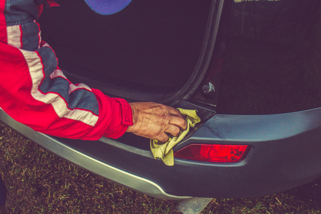 Car detailing - the man holds the microfiber in hand and polishes the car. 免版税图像