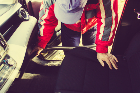 Man hoovering seat of car during car cleaning.Remove dust with a vacuum cleaner during car cleaning car wash