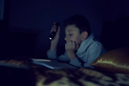 Boy reading a book with a flashlight in dark room
