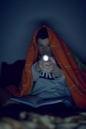 Boy reading a book with a flashlight under a blanket Banco de Imagens