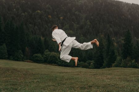 Martial art of karate, a man in a kimono with black belt trains on the mountain,free space. Imagens