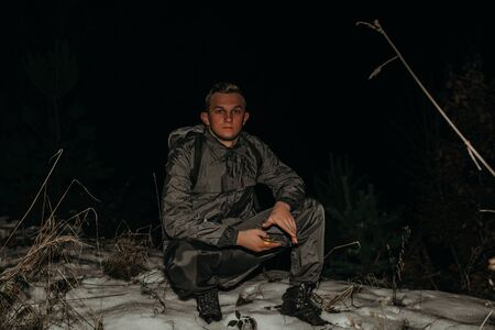 Male hikers in clothes for hiking and flashlights on winter mountain at night.