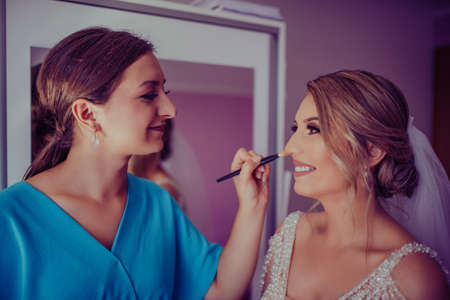 stylish happy bride dressing in dress, smiling to bridesmaids, at window, rustic wedding morning preparation. bridal getting ready. emotional moment. space for text. black white photo Foto de archivo