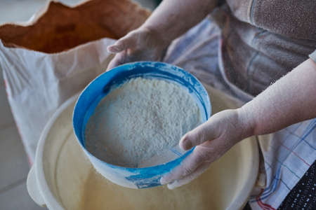 Woman hands sifting flour with flour filter