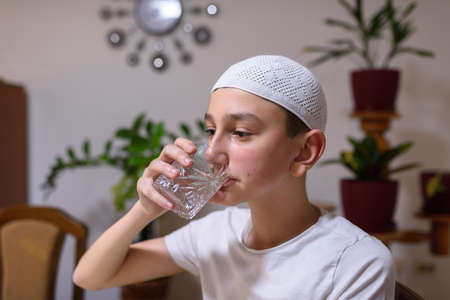 A boy in an Islamic costume drinks water during Iftar in the month of Ramadan