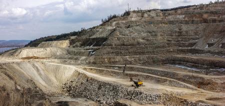 Żółta koparka wewnątrz odkrywkowej kopalni. Duży kamieniołom minerałów i skał.