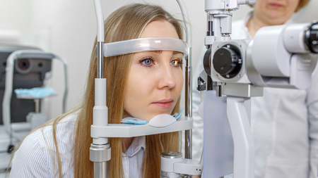Ophthalmology - ophthalmologist checks the eyes of a girl