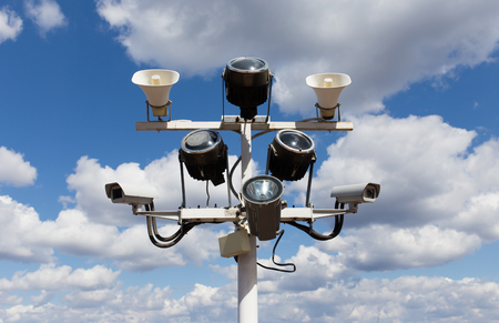 Two security cameras, floodlights and loudspeakers on blue sky background Stock Photo