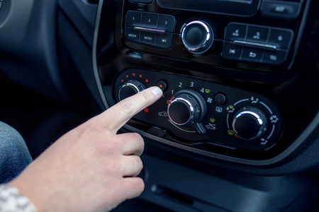 blank screen: male hand pressing button in modern car. Man adjusts the temperature of the car air conditioner