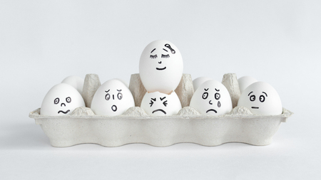 Eggs with funny faces in the package on a white background. Easter Concept Photo. Eggs. Faces on the eggs