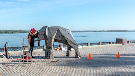 Welder on the street makes an elephant of iron, urban concept