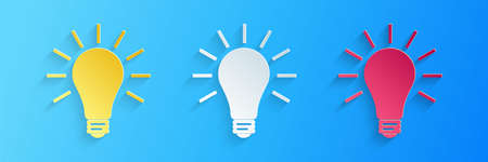 Paper cut Light bulb with rays shine icon isolated on blue background. Energy and idea symbol. Lamp electric. Paper art style. Vector Ilustracja