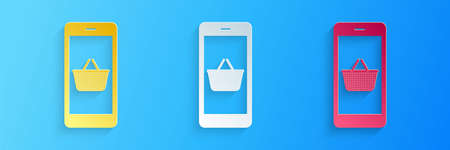 Paper cut Mobile phone and shopping basket icon isolated on blue background. Online buying symbol. Supermarket basket symbol. Paper art style. Vector