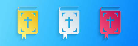 Paper cut Bible book icon isolated on blue background. Holy Bible book sign. Paper art style. Vector