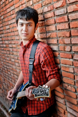 Handsome young musician playing the guitar and singing at the red wall. photo