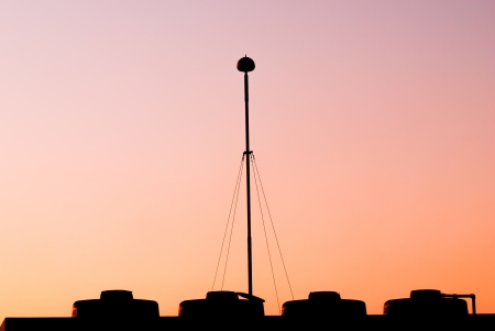 The lightning rod on the roof-tile taken when sunset photo