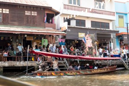 Samutsongkhram, Thailand- January 4, 2014: Tourists visiting the Amphawa Floating market making boat tour, the most popular floating market in Thailand.