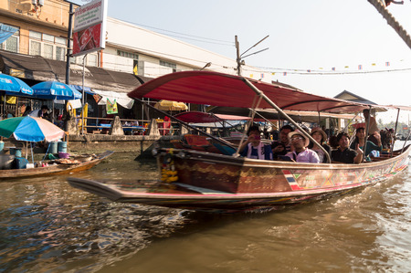 Samutsongkhram, Thailand- January 4, 2014: Tourists visiting the Amphawa Floating market making boat tour, the most popular floating market in Thailand.