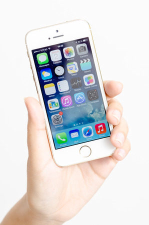 A womans hand holding an iPhone 5s  Close-up shot of her hand and the iPhone homescreen  The cellular phone is produced by Apple Computer, Inc