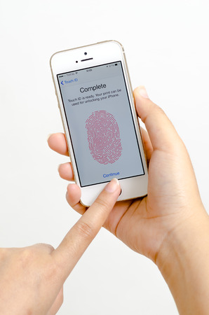Woman hands holding and touching an Apple iPhone 5s color gold showing fingerprint scan interface  iPhone 5s is a smart phone produced by Apple Computer, Inc