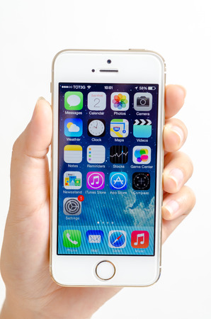 holding close: A womans hand holding an iPhone 5s  Close-up shot of her hand and the iPhone homescreen  The cellular phone is produced by Apple Computer, Inc
