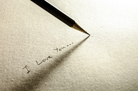 Pencil with paper writing I love you photo