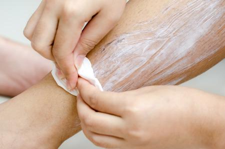 shaving cream: Body hygiene: Woman depilates - scrubs hair removal cream off her leg