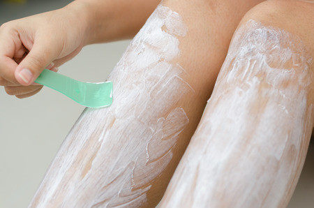 Body hygiene: Woman depilates - scrubs hair removal cream off her leg