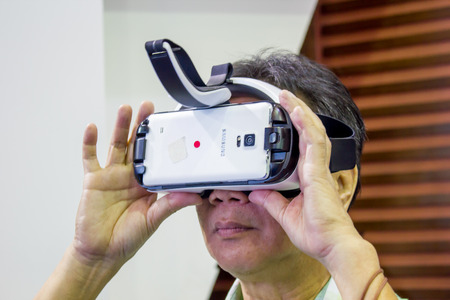 samsung: BANGKOK, THAILAND - October 5, 2014  :The  Man ues the Samsung Galaxy Note 4 and Samsung Galaxy  Gear VR, is an Android smartphone produced by Samsung Electronics at Thailand Mobile Expo 2014